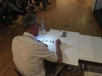 Dem Kalligraphen über die Schulter geschaut – Brody Neuenschwander erläutert ganz praktisch, wie aus einem Piktogramm ein Buchstabe wird. Foto: Diözesanmuseum Paderborn