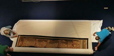 Nach der Ankunft in Paderborn wird der kostbare Rubensteppich ganz vorsichtig abgerollt und ausgelegt.